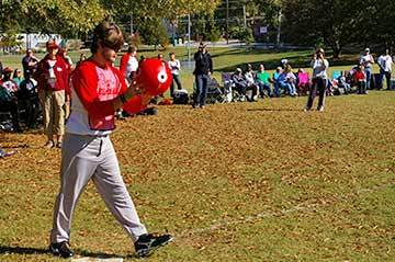 A player in a red jersey holds kickball up before kicking.